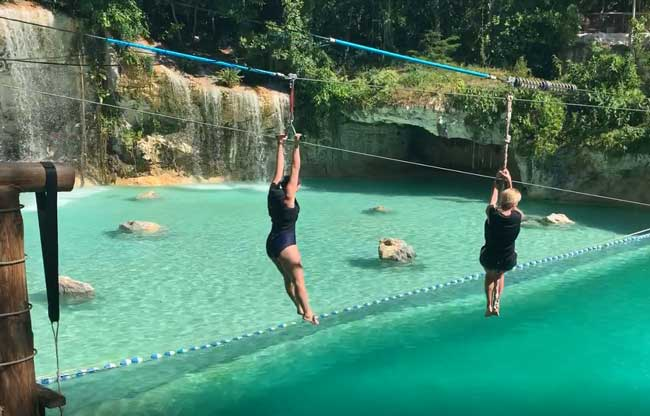 The author (right) and her friend, Lesli, zip over the Saltos Azules at Scape Park in the Dominican Republic. Photo courtesy Janna Graber