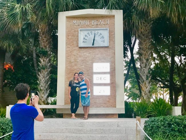 Couple takes picture in front of Miami Beach clock.