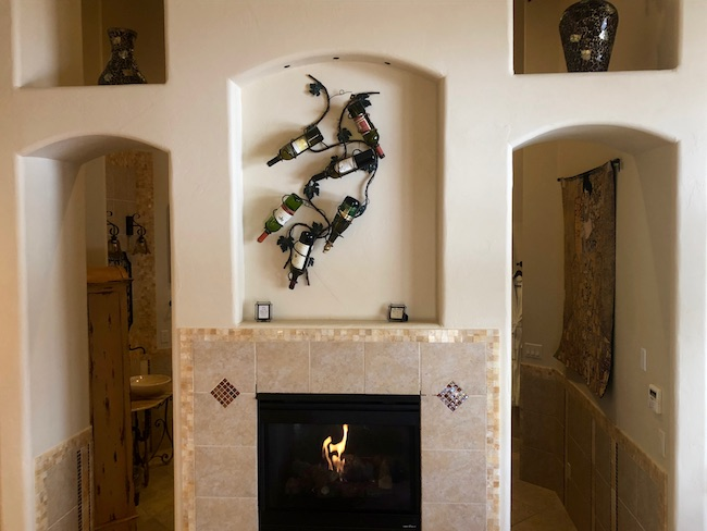 Fireplace wall opposite the bed. Photo by Claudia Carbone