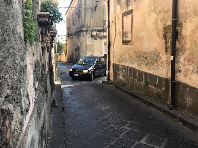 Car turning left onto alley like road.