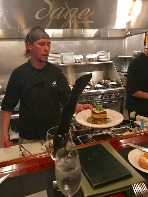 Chef presenting meal from open kitchen at Sage Room in Hilton Head