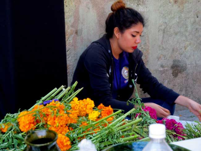 A young girl in Oaxaca's Central Market sells cempasuchiltes to cemetery goers.
