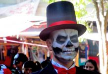"A man playing the part of a ""catrin"" donned a top hat and tuxedo at Day of the Dead in Oaxaca, Mexico. Photo by Carol L. Bowman"