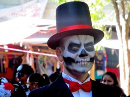 """A man playing the part of a """"catrin"""" donned a top hat and tuxedo at Day of the Dead in Oaxaca, Mexico. Photo by Carol L. Bowman"""