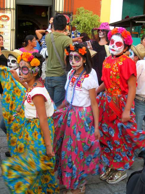 Parade participants called comparsas wear calavera faces and included children, teens, adults, and elders. Photo by Carol L. Bowman