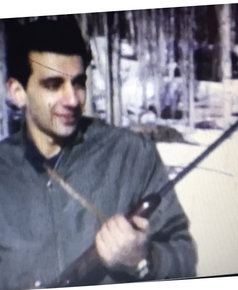 Ron Khoury holding a rifle and smiling.
