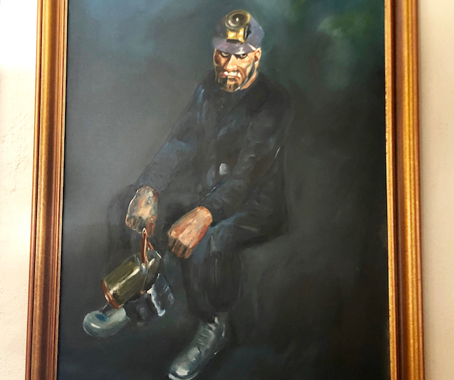 This painting in the living room depicts a miner and his weary plight. Photo by Claudia Carbone