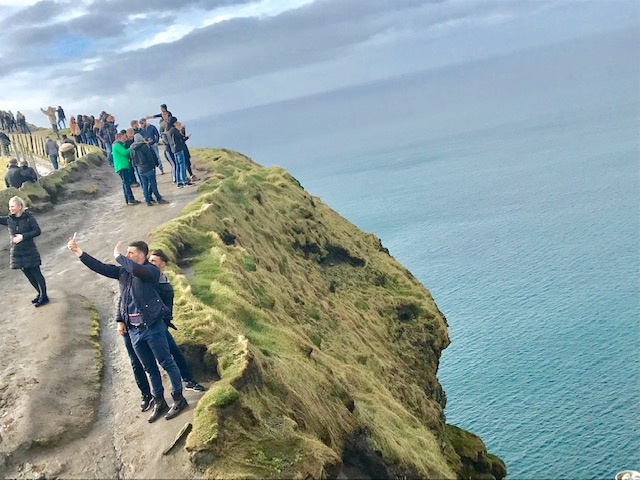 Tourists take selfies along Cliffs of Moher.