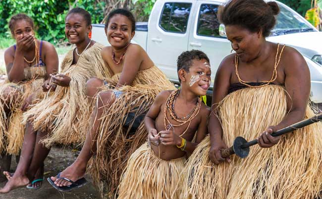A Langalanga family, from Malaita Island, Ester, Margaret, Julie, and two siblings are members of the group who continue to make and use shell money, relax after demonstrating the process for visitors. Seen here in Mbokana Village, in Honiara, they come to the capital to sell shell money necklaces, and the ten-foot shell chains they use as barter and as a bride price. Photo ©Steve Haggerty