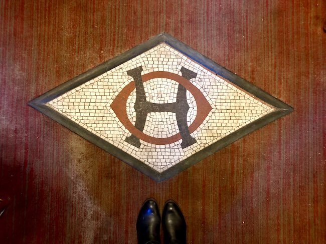 Original logo on the floor of the entrance. Photo by Claudia Carbone