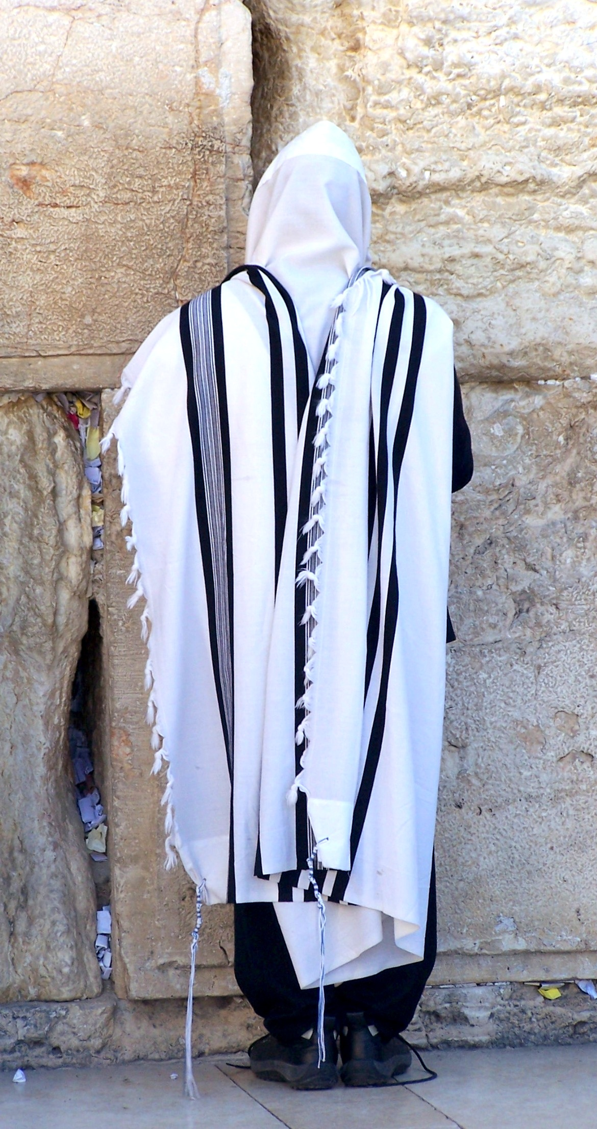 Wall ceremonial garb for Yom Kippur; white kittel robes, draped with black and white prayer shawls called tallits and a white hood or kippah for the head. Photo by Carol L. Bowman.
