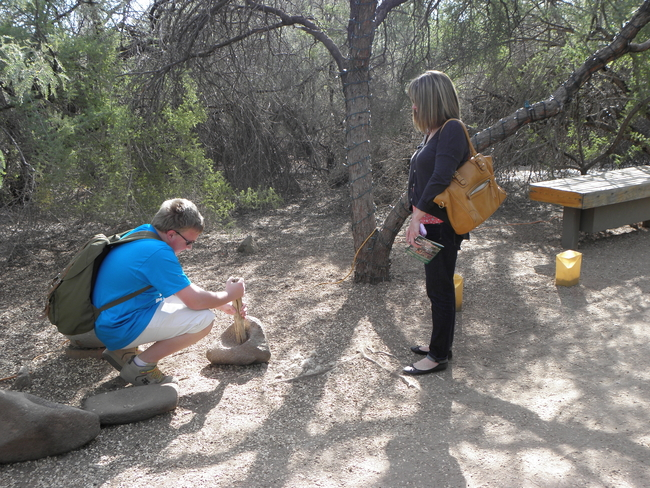 Trying out a Grinding Stone at the Desert Botanical Garden in Scottsdale, Arizona, by Victor Block