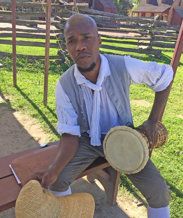 """An interpreter at Colonial Williamsburg demonstrates how enslaved Africans used drums to communicate. The enslaved preserved many traditions from their African ancestors. The drums could be used to convey messages, such as """"The overseer is coming -- everyone look busy!"""" It was one of the many ways that enslaved people fought back and resisted slavery."""