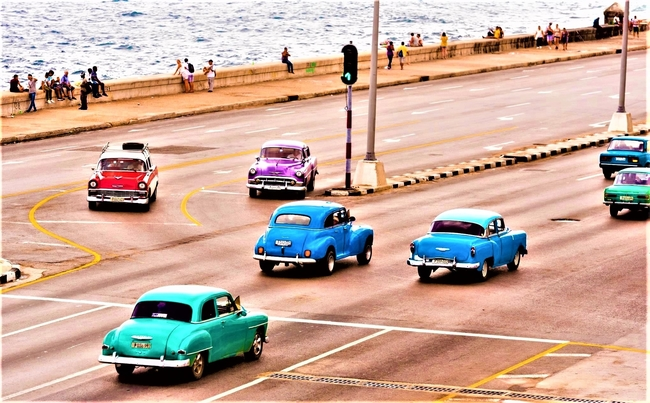 People and vintage American-made cars share the Malecon in Havana, Cuba. Photo by Gerald Groteueschen/Dreamstime.com