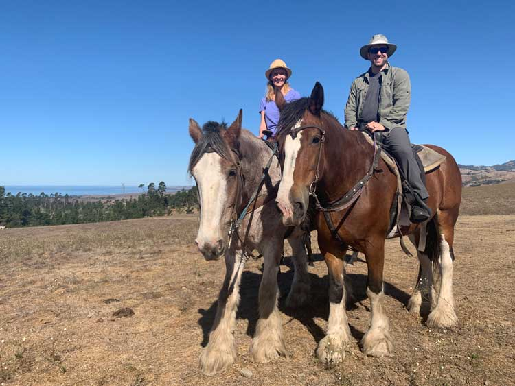 The author and her husband riding at Covell's Clydesdales in Cambria, California