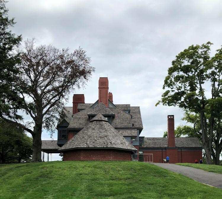 An eye catching sideview of the house at Sagamore Hill with the Ice House in front.