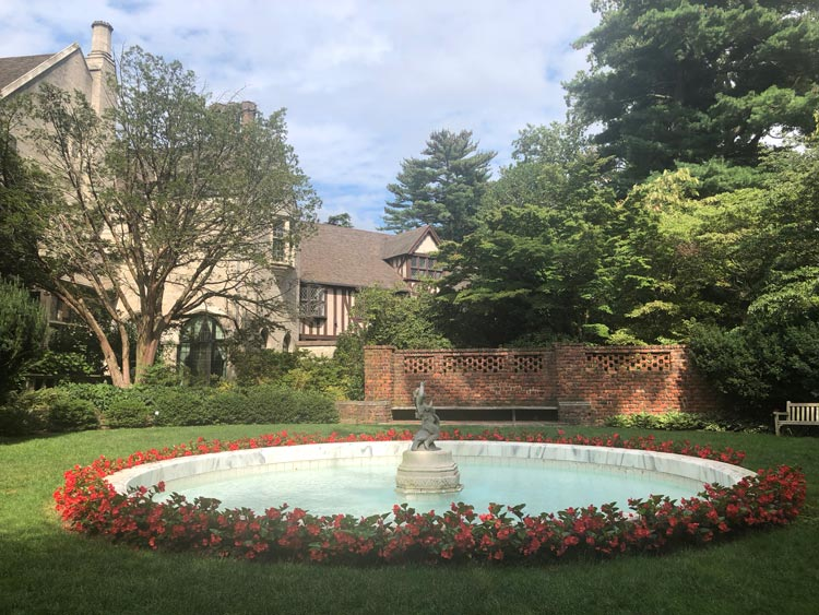 Glimpses of Coe House Mansion beyond the fountain at Planting Fields Arboretum