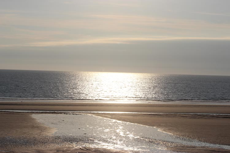 The sun beginning to set over a silvery sea in Jersey in the Channel Islands.