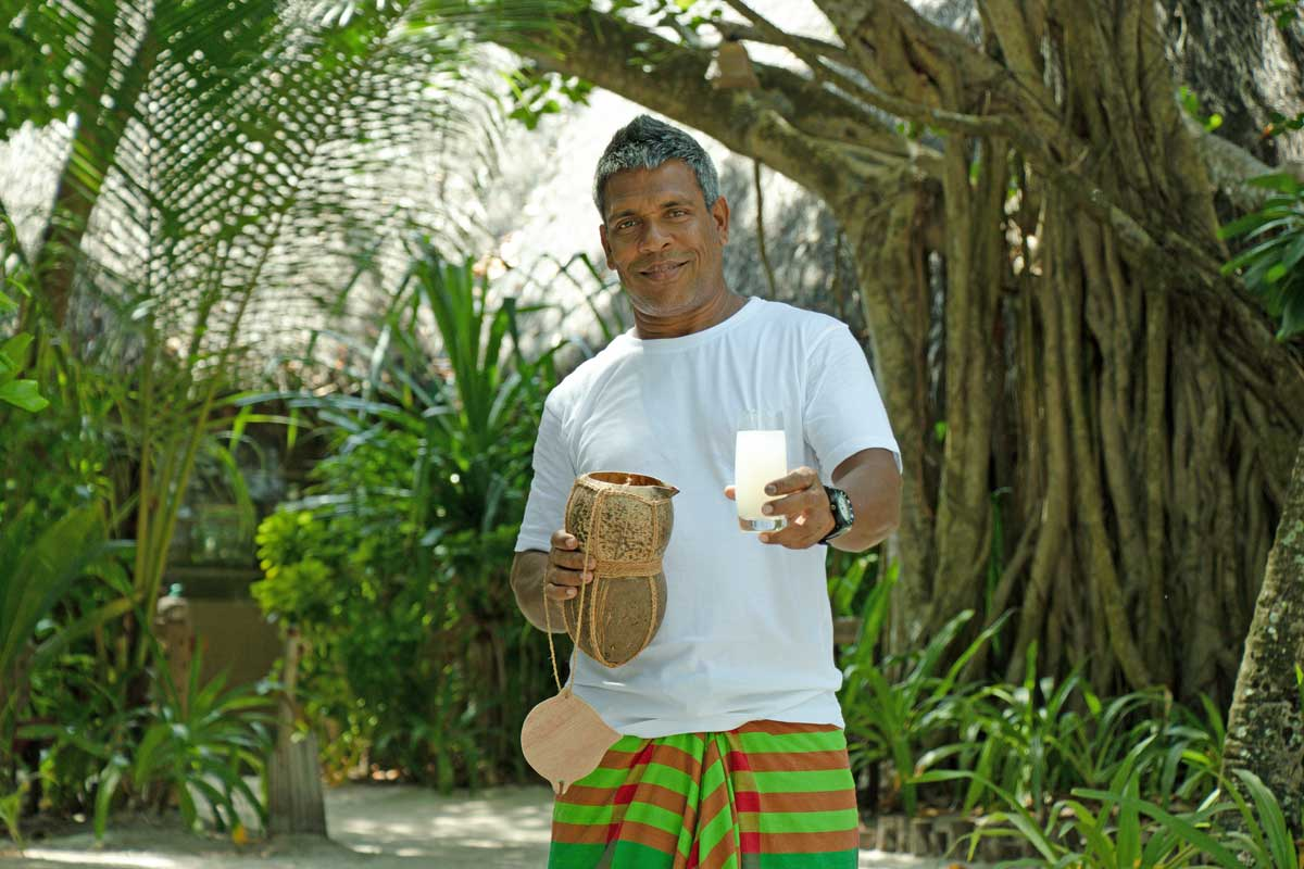 Haroon Ibrahim offers guests a refreshing toddy drink at Coco Palm Dhuni Kolhu in the Maldives