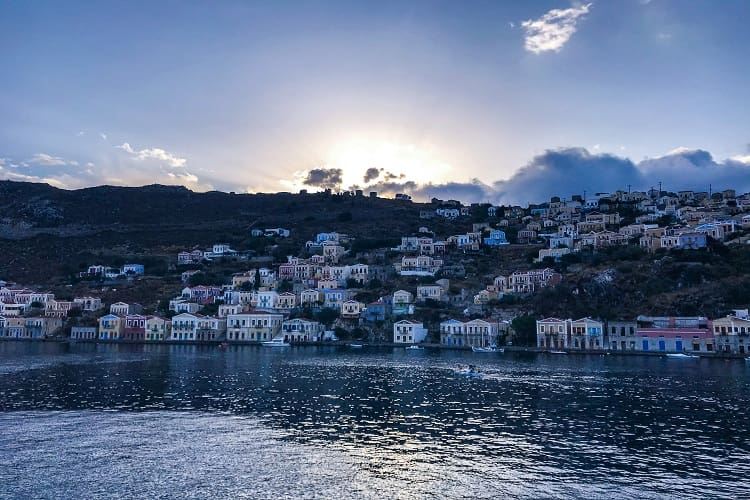 Sun peaks over the rocky mountains in Symi, Greece