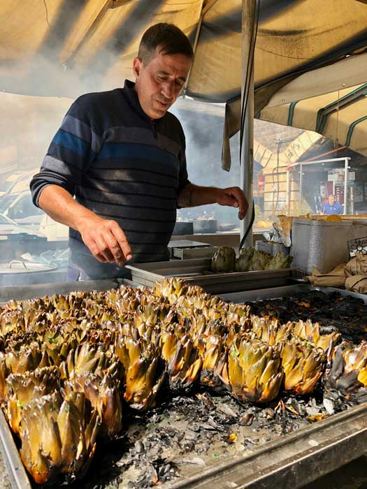 The vendor gave each prickly artichoke a generous slathering of olive oil and finely chopped parsley