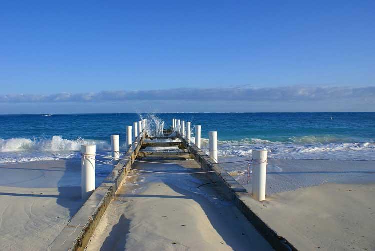 Waves crashing against the jetty on a sunny beach walk.