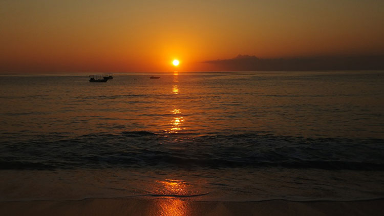 The sun setting over the Turks and Caicos Islands and boats also enjoy the view.