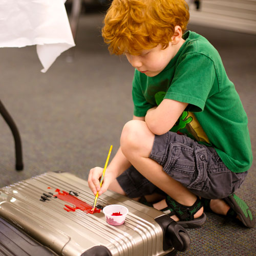 Boy claims lost luggage item by painting on it at the Unclaimed Baggage Store