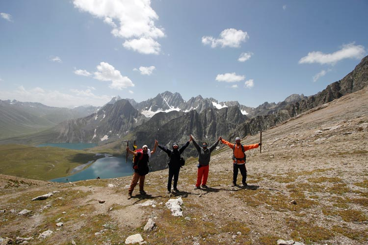 Trekkers from Glacier Trekking and Mountaineering Club, one of the oldest adventure sports club from the Kashmir Valley, gesture while conquering Gadsar pass, with Kishansar and Vishansar Lakes in the background