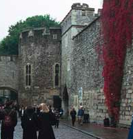 Tourists walk through the flower lined castle walls of the London Tower.