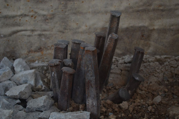 Worn out chisels stuck into the soil.