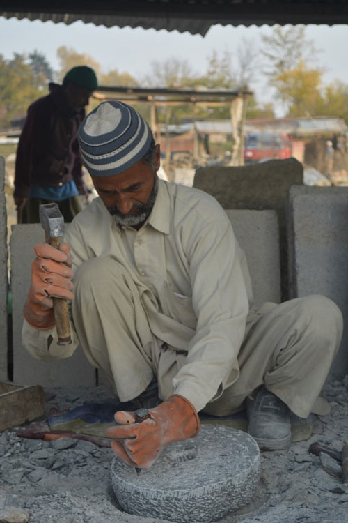 Mohammad Shabaan in the stone carving process of making millstones.