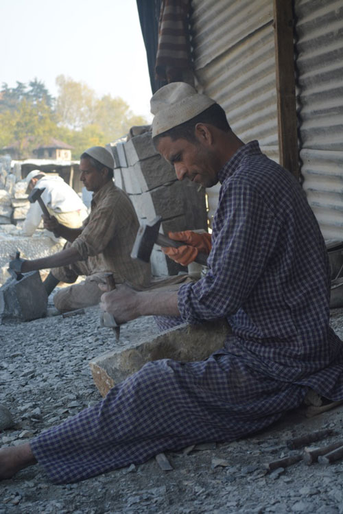 Men at work carving giant stones with stone tools.