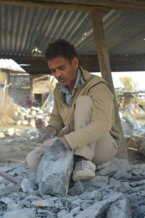 Ali Mohammad at work carving on a pile of stones.