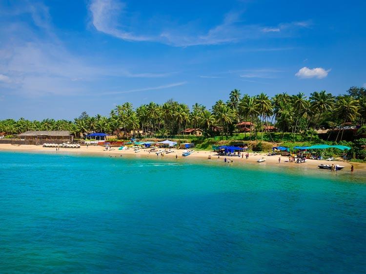 Tourists soak up the sun along the bright beach in Goa, India.