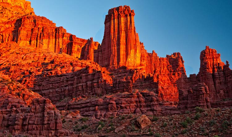 Red rock cliffs glow in the sunset along the Colorado river in Moab, Utah.