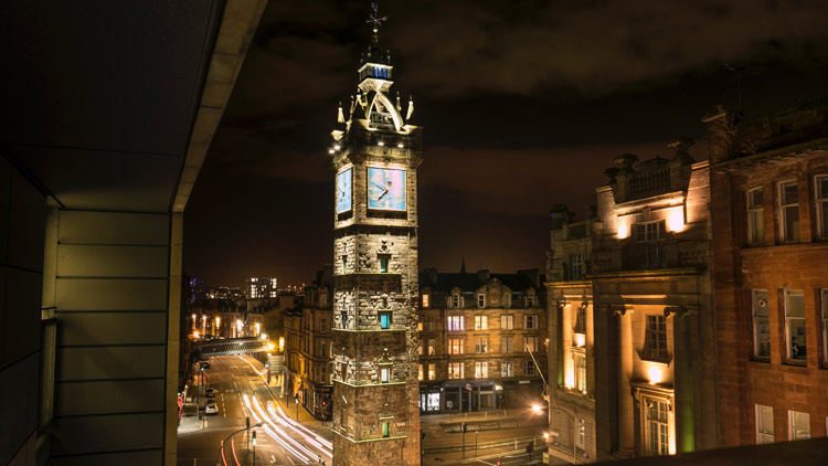 Tolbooth clock tower shining as bright as the city of Glasgow in the evening.
