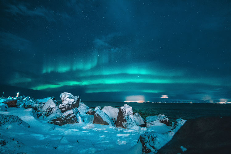Stunning northern lights glow through the night along the coasts of Iceland.