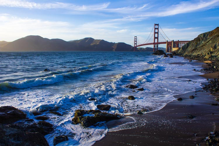 The Golden Gate Bridge in the distance crossing the Pacific ocean along the coast in California, USA.