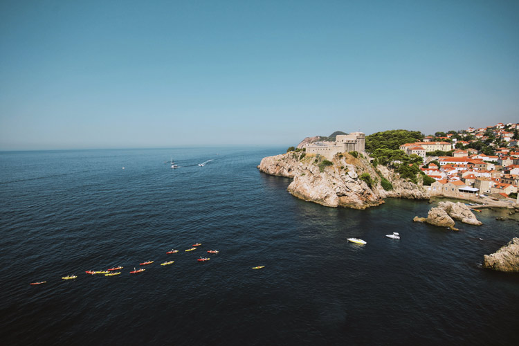 Kayaking group paddles back to campgrounds on shore in Dubrovnik, Croatia.