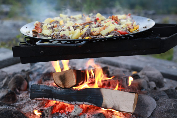 A traditional campfire meal of reindeer, Arctic char, potatoes and peppers.