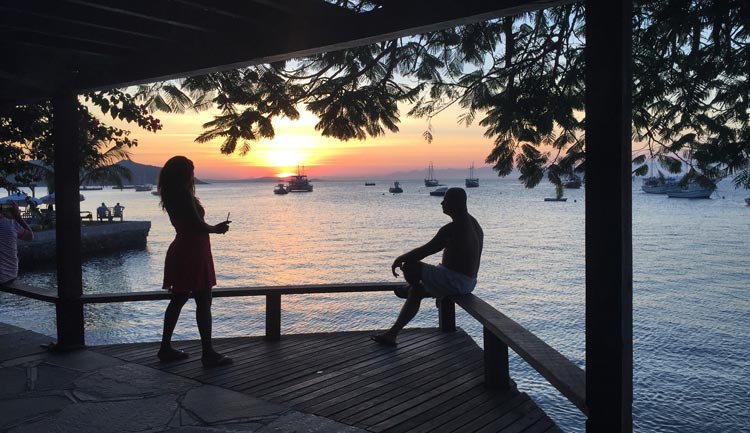 Two people admiring the sunset at Buzios beach.
