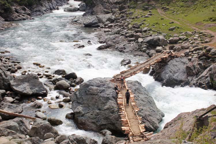 Hikers cross a makeshift log bridge over a stream in Kongwattan area of Kulgam district of south Kashmir region. This trail leads to Kounsarnag alpine lake in the Pir Panjal mountain range in Kashmir.
