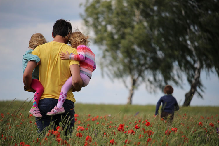 Father and children make a stop to explore the field full of wildflowers.