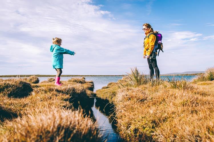 Mom and daughter enjoying a backpack trip along lake.