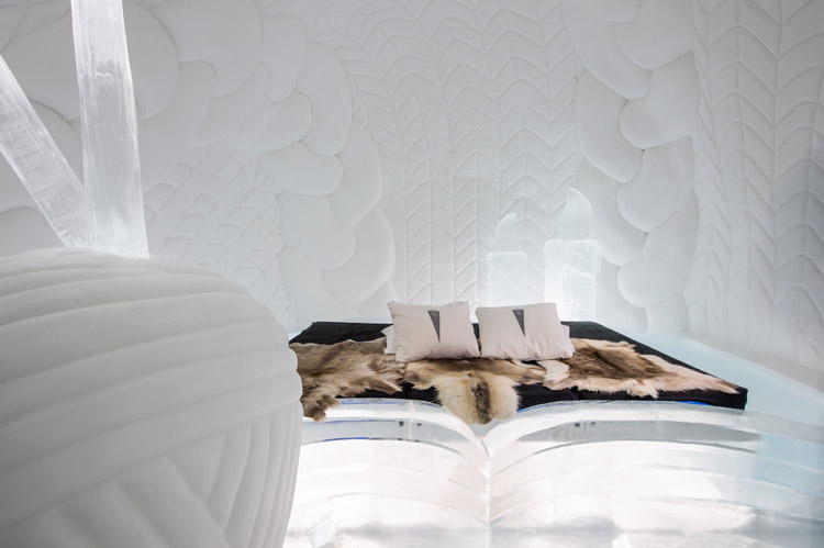 A modern room in the Icehotel with an ice bed to lounge on.