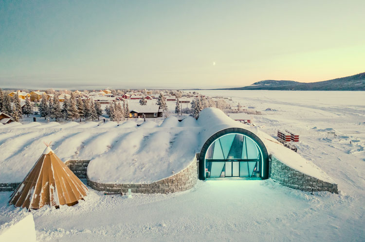 The Icehotel glowing under a blanket of snow.