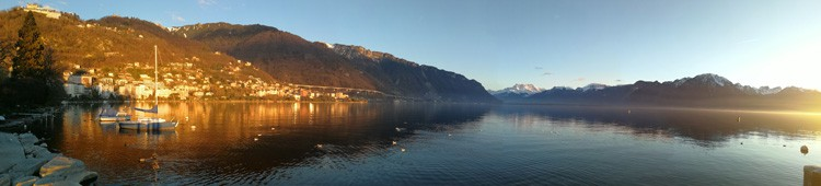 A panoramic view of Lake Geneva with the town of Montreux shining in the sun.