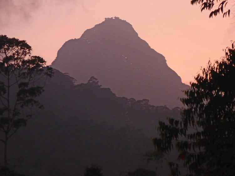 Adam's Peak looms above Dalhousie village in a purple haze at dusk.