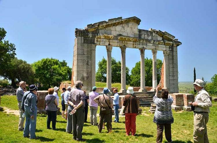 Tourists admiring the ancient ruins of Apollonia city at Archaeological Park.